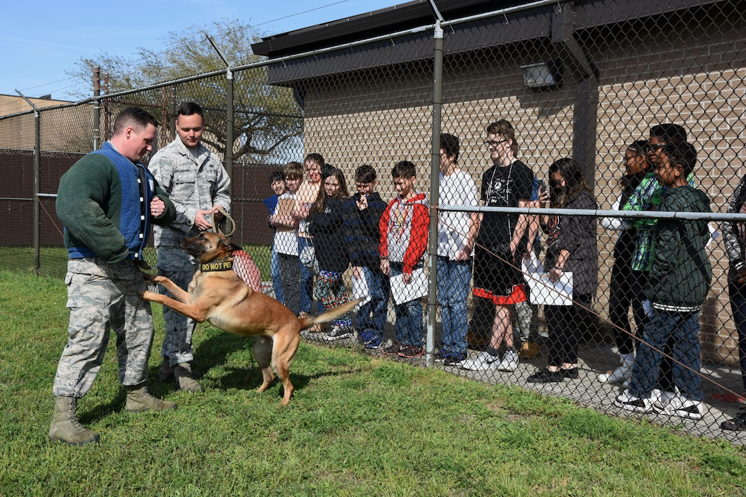 Senior Airmen Timothy Poissant, and Douglas Sullivan, 81st Security Forces Squadron military working dog handlers, and Zeno, 81st SFS military working dog, stage a scenario for school-aged children at the 81st SFS canine facility during Biloxi Career Exploration Day March 2, 2017, on Keesler Air Force Base, Miss. The children also toured the 334th Training Squadron air traffic control school, 335th TRS weather facility and the Keesler Fire Department. (U.S. Air Force photo by Kemberly Groue)
