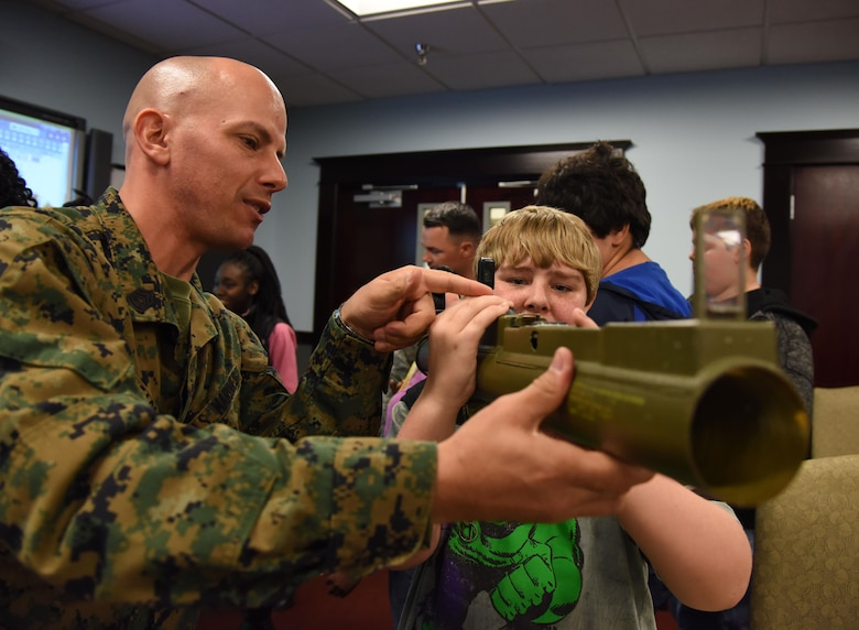 U.S. Marine Corps Gunnery Sgt. Michael Heacock, Keesler Marine Detachment instructor, shows Orion Jenson-Robertson an antitank rocket launcher at the 335th Training Squadron weather facility during Biloxi Career Exploration Day March 2, 2017, on Keesler Air Force Base, Miss. The school-aged children also toured the 334th TRS air traffic control school, 81st Security Forces Squadron canine facility and the Keesler Fire Department. (U.S. Air Force photo by Kemberly Groue)