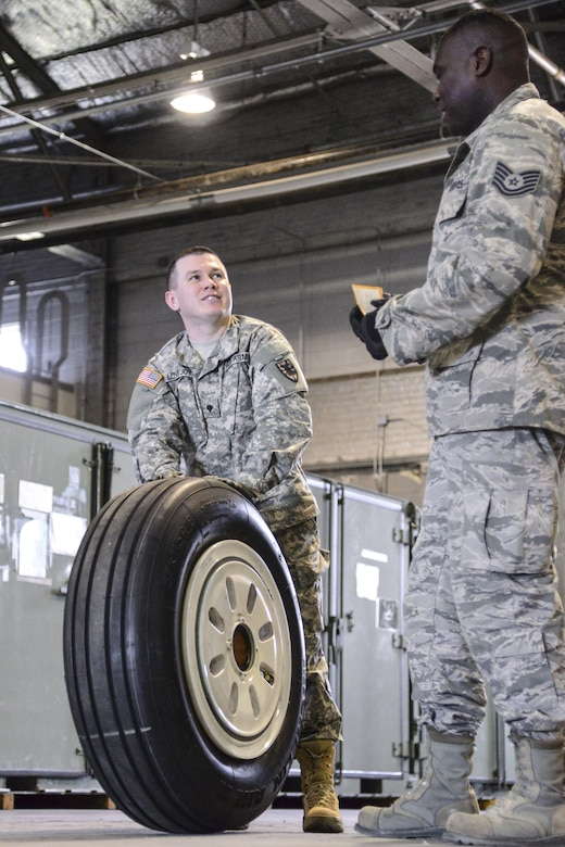 U.S. Army Spc. Eugene Lovejoy, 368th Seaport Operations Company, 11th Transportation Battalion, 7th Transportation Brigade (Expeditionary) motor pool clerk, receives guidance from U.S. Air Force Tech. Sgt. Jeremy Roberts, 733rd Logistic Readiness Squadron readiness spares package NCO in charge,  on how to properly load a tire at Joint Base Langley-Eustis, Va., March 2, 2017. The 733rd LRS worked with the 7th Transportation Brigade's supply specialists during a week-long training to showcase the Air Force's supply management processes. (U.S. Air Force photo by 1st Lt. Mahalia Frost)