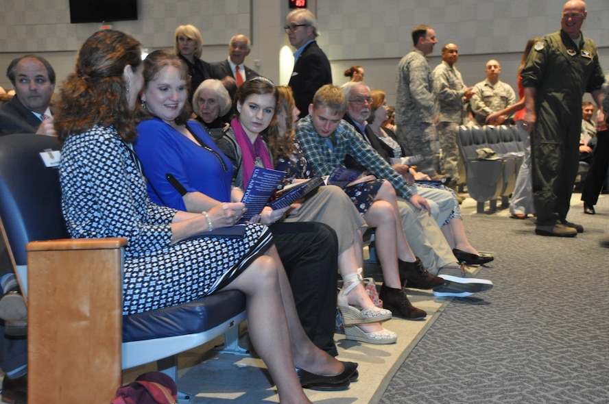 Sandy Stokes (left) wife of 22nd Air Force commander Maj. Gen. John Stokes, sits with the Ostrat family before Col. Kenneth Ostrat's Assumption of Command ceremony March 5 at Maxwell Air Force Base. Ostrat returns to the 908th Airlift Wing after his previous stint as the director of operations of the wing's 357th Airlift Squadron from July 2008 until December 2012. (U.S. Air Force photo by Bradley J. Clark)