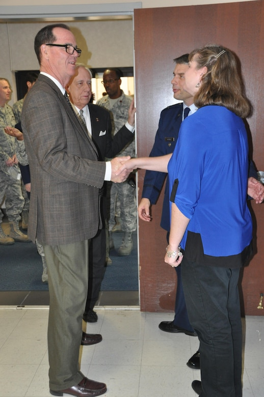 Joe Green, staff member of the Montgomery Chamber of Commerce, shakes hands with Lora Ostrat, while Tom Albrecht, Montgomery civic leader chats with newly minted commander of the 908th Airlift Wing, Col. Ken Ostrat. Green and Albrecht congratulated the Ostrats following his Assumption of Command ceremony March 5 at Maxwell Air Force Base. (U.S. Air Force photo by Bradley J. Clark)