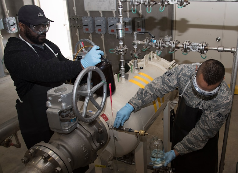Troy Farris, left, a fuels laboratory lead technician with the 35th Logistics Readiness Squadron, and U.S. Air Force Senior Airman Ken Leon Guerrero, right, a fuels laboratory technician with the 35th LRS, draw Jet Propellant 8 at Misawa Air Base, Japan, March 6, 2017. The fuel is checked for particulate matter, which consist of dirt, grime and water levels in the fuel that could negatively affect the F-16 Fighting Falcon flying mission. (U.S. Air Force photo by Airman 1st Class Sadie Colbert)