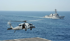 An MH-60S Sea Hawk helicopter attached to the Dragon Whales of Helicopter Sea Combat Squadron (HSC) 28 drops supplies on the flight deck of the aircraft carrier USS George H.W. Bush (CVN 77) during a vertical replenishment. The guided-missile destroyer USS Truxton (DDG 103) is in the background. George H.W. Bush is supporting maritime security operations and theater security cooperation efforts in the U.S. 5th Fleet area of operations. (U.S. Navy photo by Mass Communication Specialist 3rd Class Margaret Keith/Released)