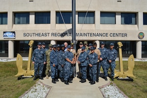 """Capt. Dave Gombas, Commanding Officer (back row, center right); Capt. Gary Martin (back row, center left), Executive Officer and Bob Wright (back row, center left), Executive Director at Southeast Regional Maintenance Center (SERMC) are surrounded by Navy Counselor Chief Shanika Jones (4th from left) and a few of the SERMC Sailors who reenlisted during Fiscal Year 2016. SERMC was recognized for successful Sailor programs that form the foundation of a successful retention effort, earning the coveted """"Golden Anchors"""" award."""