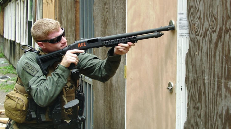 Sgt. Trenton Hansen, a Special Reaction Team member from the Marine Corps Base Quantico Provost Marshals Office, uses a Military Enhancement Kit to breach open a door. The MEK provides versatile capabilities to Marine units trained to engage on breaching missions. The kit builds upon the Mossberg M500A2, but gives Marines a shorter, vented breaching barrel and three interchangeable buttstock attachments, including the collapsible buttstock featured in this photo. (U.S. Marine Corps photo by Alan Matthews)