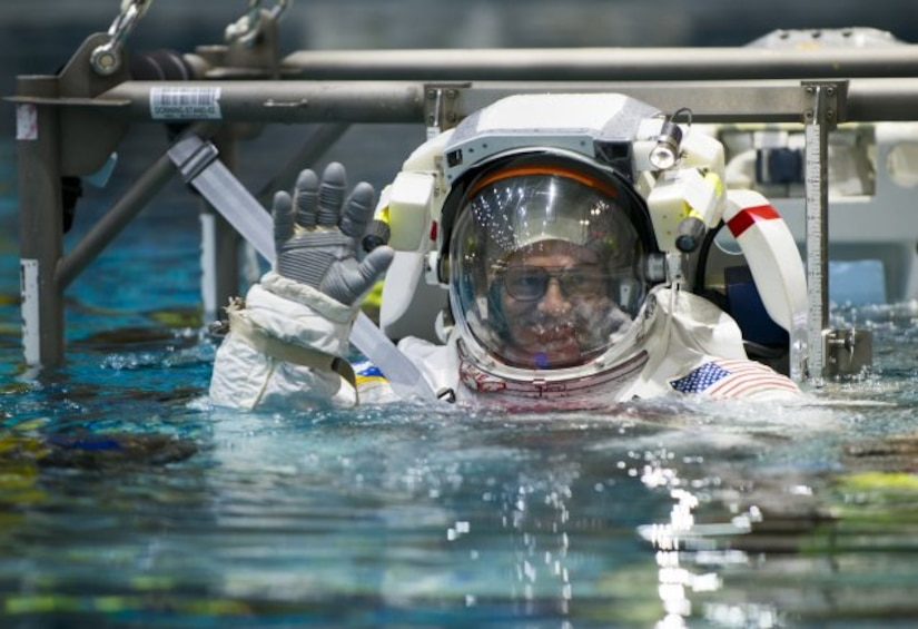 Mark Vande Hei, a retired Army colonel, waves as he is lowered into NASA's Neutral Buoyancy Laboratory pool near Johnson Space Center in Houston as part of training, March 1, 2017. The pool is one of the world's largest at 202 feet long and 40 feet deep, and is big enough to hold a replica of the International Space Station. Vande Hei is preparing for his first space mission, which is scheduled for mid-September. DoD photo by Sean Kimmons