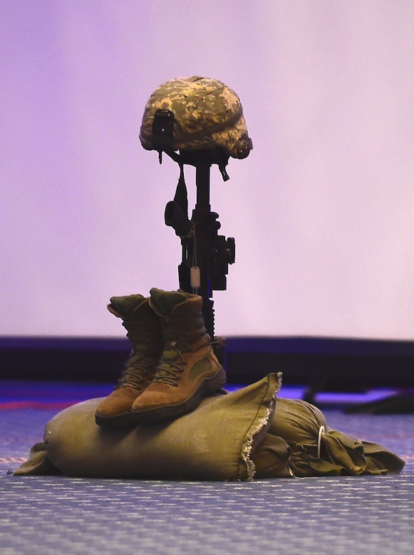 A an M-4 Carbine assault rifle with a helmet, boots and sandbags is displayed in honor of fallen service members, prisoners of war and those missing in action during the 2017 Outstanding Airmen of the Year banquet at the Bayview Community Center at Langley AFB, Virginia, March 8, 2017. Most official Air Force banquets and ceremonies have a moment of silent during events to pay tribute to more than 150, 000 Americans who are missing in action or have been held as prisoners of war. (U.S. Air Force photo by Senior Airman Kimberly Nagle)