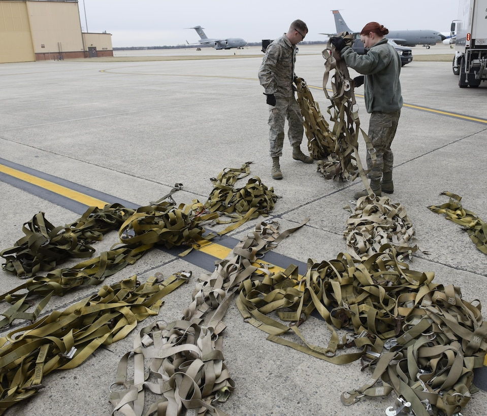 "Joint Records Team (JRT) members prepare to receive presidential materials outside of a hangar on Joint Base Andrews, Md., Feb. 14, 2017. JRT members included Airmen assigned to the Air Force District of Washington (AFDW) and Soldiers from the U.S. Army's 3rd Infantry Division ""The Old Guard"" worked in concert with Presidential Material Handlers from the National Archives and Records Management (NARA) over several months to ensure the safe movement of the records and artifacts gathered during the eight years of President Obama's administration. The JRT was tasked with helping to inventory, prepare for shipping, palletize and load several tons of paper records, terabytes of electronic records, and thousands of artifacts. Along with several truck shipments the bulk of the materials were loaded onto and Air Force C-5 Galaxy cargo aircraft brought in from Dover Air Force Base, Del., and were then flown to Chicago, Ill., where they were placed in secure storage until completion of Obama's Presidential Library. The library is part of the presidential library system, which is administered by the National Archives and Records Administration. (U.S. Air Force photo/Jim Varhegyi) (released)"