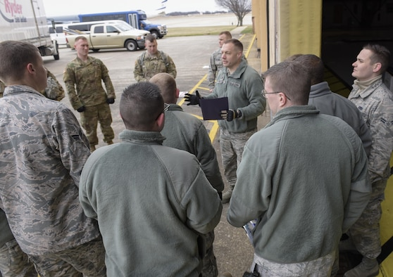 """The Joint Records Team (JRT) operations officer U.S. Air Force Capt. Nathan Tilton briefs JRT members prior to receiving presidential materials at a hangar on Joint Base Andrews, Md., Feb 14, 2017. JRT members included Airmen assigned to the Air Force District of Washington (AFDW) and Soldiers from the U.S. Army's 3rd Infantry Division """"The Old Guard"""" worked in concert with Presidential Material Handlers from the National Archives and Records Management (NARA) over several months to ensure the safe movement of the records and artifacts gathered during the eight years of President Obama's administration. The JRT was tasked with helping to inventory, prepare for shipping, palletize and load several tons of paper records, terabytes of electronic records, and thousands of artifacts. Along with several truck shipments the bulk of the materials were loaded onto and Air Force C-5 Galaxy cargo aircraft brought in from Dover Air Force Base, Del., and were then flown to Chicago, Ill., where they were placed in secure storage until completion of Obama's Presidential Library. The library is part of the presidential library system, which is administered by the National Archives and Records Administration. (U.S. Air Force photo/Jim Varhegyi) (released)"""