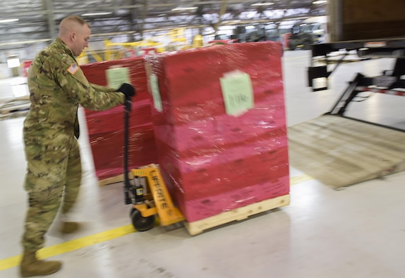 """The Joint Records Team (JRT) officer in charge (OIC) of team DC, U.S. Army Capt. Scott McInernie, moves a pallet full of presidential records in a hangar on Joint Base Andrews, Md., Feb 14, 2017. The JRT was made up of Airmen assigned to the Air Force District of Washington (AFDW) and Soldiers from the U.S. Army's 3rd Infantry Division """"The Old Guard"""" worked in concert with Presidential Material Handlers from the National Archives and Records Management (NARA) over several months to ensure the safe movement of the records and artifacts gathered during the eight years of President Obama's administration. The JRT was tasked with helping to inventory, prepare for shipping, palletize and load several tons of paper records, terabytes of electronic records, and thousands of artifacts. Along with several truck shipments the bulk of the materials were loaded onto and Air Force C-5 Galaxy cargo aircraft brought in from Dover Air Force Base, Del., and were then flown to Chicago, Ill., where they were placed in secure storage until completion of Obama's Presidential Library. The library is part of the presidential library system, which is administered by the National Archives and Records Administration. (U.S. Air Force photo/Jim Varhegyi) (released)"""