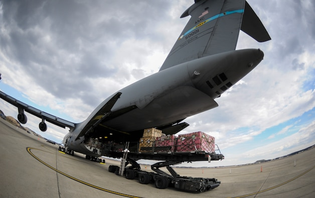 "Presidential materials are loaded onto a C-5 Galaxy cargo aircraft at Joint Base Andrews, Md., Feb. 15, 2017. The Joint Records Team (JRT) made up of Airmen assigned to the Air Force District of Washington (AFDW) and Soldiers from the U.S. Army's 3rd Infantry Division ""The Old Guard"" worked in concert with Presidential Material Handlers from the National Archives and Records Management (NARA) over several months to ensure the safe movement of the records and artifacts gathered during the eight years of President Obama's administration. The JRT was tasked with helping to inventory, prepare for shipping, palletize and load several tons of paper records, terabytes of electronic records, and thousands of artifacts. Along with several truck shipments the bulk of the materials were loaded onto and Air Force C-5 Galaxy cargo aircraft brought in from Dover Air Force Base, Del., and were then flown to Chicago, Ill., where they were placed in secure storage until completion of Obama's Presidential Library. The library is part of the presidential library system, which is administered by the National Archives and Records Administration. (U.S. Air Force photo/Jim Varhegyi) (released)"