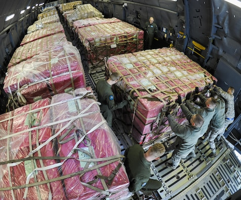 """Presidential materials are loaded onto a C-5 Galaxy cargo aircraft at Joint Base Andrews, Md., Feb. 15, 2017. The Joint Records Team (JRT) made up of Airmen assigned to the Air Force District of Washington (AFDW) and Soldiers from the U.S. Army's 3rd Infantry Division """"The Old Guard"""" worked in concert with Presidential Material Handlers from the National Archives and Records Management (NARA) over several months to ensure the safe movement of the records and artifacts gathered during the eight years of President Obama's administration. The JRT was tasked with helping to inventory, prepare for shipping, palletize and load several tons of paper records, terabytes of electronic records, and thousands of artifacts. Along with several truck shipments the bulk of the materials were loaded onto and Air Force C-5 Galaxy cargo aircraft brought in from Dover Air Force Base, Del., and were then flown to Chicago, Ill., where they were placed in secure storage until completion of Obama's Presidential Library. The library is part of the presidential library system, which is administered by the National Archives and Records Administration. (U.S. Air Force photo/Jim Varhegyi) (released)"""