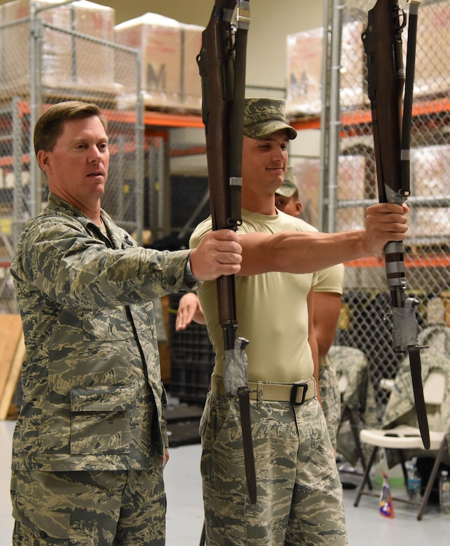 Col. C. Mike Smith, 81st Training Wing vice commander, learns rifle-holding techniques from Senior Airman Tyler Reynolds, U.S. Air Force Honor Guard Drill Team member, following a performance of the team's new routine for base leadership at the Roberts Consolidated Aircraft Maintenance Facility March 2, 2017, on Keesler Air Force Base, Miss. The team developed a new routine at Keesler during the past five weeks that they will use throughout the year. The team will unveil the routine at the 81st Training Group drill down competition March 10, 2017 (U.S. Air Force photo by Kemberly Groue)