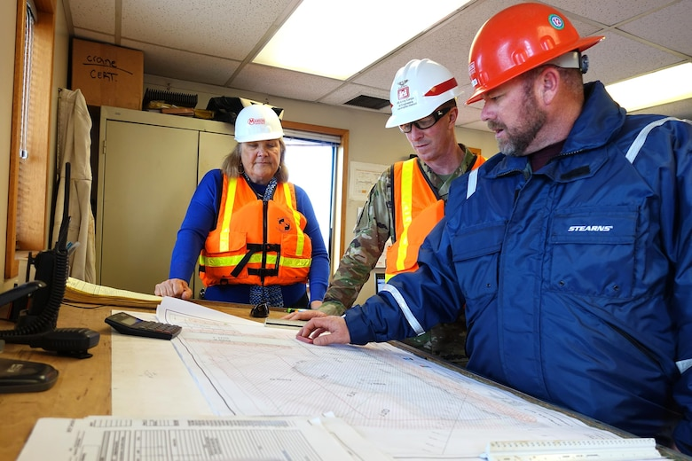A Seattle-based Manson Construction employee shows Channel Islands Harbor Director Lyn Krieger and Los Angeles District Commander Col. Kirk Gibbs the hydrographic survey map of the area the hydraulic cutter-head suction dredge H.R. Morris will dredge Feb. 14. Manson, the Corps' contractor for the project, piped the dredged material to nearby Hueneme Beach to replenish sand lost to erosion.