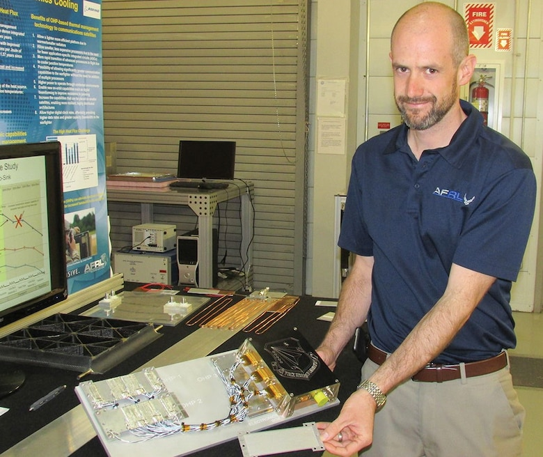 Brent Taft, Air Force Research Laboratory Space Vehicles Directorate thermal systems lead, shows an oscillating heat pipe system designed for an upcoming flight experiment, top, and an oscillating heat pipe by itself. The technology cools electronics systems and is nearing commercialization.