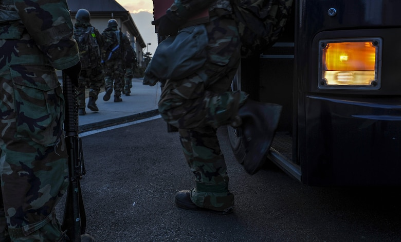 U.S. Air Force members step off a bus as they form a line as the Wolf Pack tests the ability to accept follow-on forces during exercise Beverly Pack 17-2, a no-notice training exercise at Kunsan Air Base, Republic of Korea, March 8, 2017. Kunsan airmen provide combat capabilities alongside Republic of Korea partners by participating in training, inspections and exercises throughout the year to enhance communication and interoperability between military forces so they are prepared to fight as a combined force. (U.S. Air Force photo by Senior Airman Colville McFee/Released)