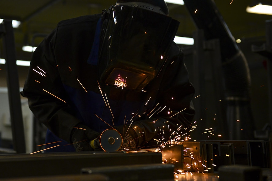 U.S. Air Force Senior Airman Kelly Huddleston, 51st Maintenance Squadron aircraft metals technology journeyman, smooths out a freshly welded piece of metal at Osan Air Base, Republic of Korea, March 7, 2017. Huddleston was fabricating an A-frame for a missile stand from scratch, running through the entire process of cutting, assembling, welding and smoothing the metal into a finished product. (U.S. Air Force photo by Staff Sgt. Victor J. Caputo)