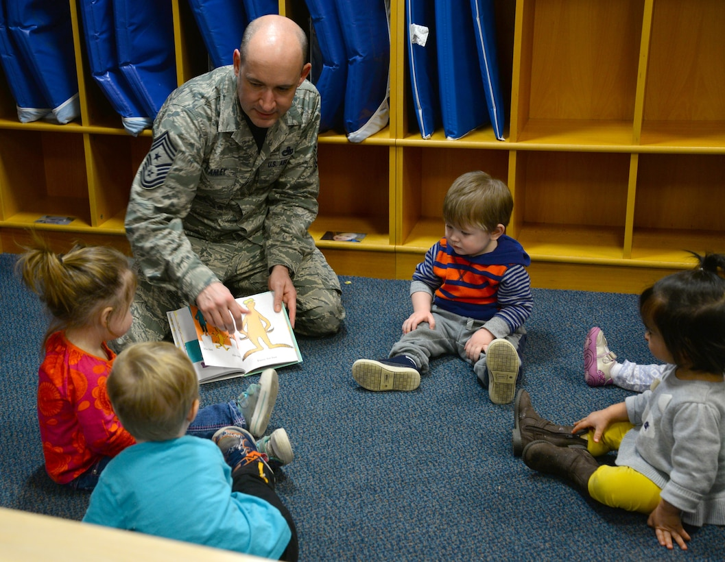 U.S. Air Force Chief Master Sgt. Curtis Stanley, 100th Air Refueling Wing command chief, center, reads a Dr. Seuss book to a circle of toddlers, March 3, 2017, at the Child Development Center on RAF Mildenhall, England. The CDC celebrated the author's birthday by hosting Team Mildenhall commanders and promoting reading to their students. (U.S. Air Force photo by Senior Airman Justine Rho)