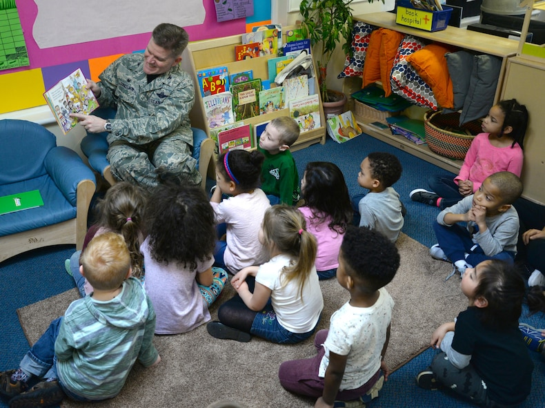 U.S. Air Force Col. Thomas Torkelson, 100th Air Refueling Wing commander, top left, reads a Dr. Seuss book to a class of children, March 3, 2017, at the Child Development Center on RAF Mildenhall, England. The CDC celebrated the author's birthday by hosting Team Mildenhall commanders and promoting reading to their students. Prior to the reading, Torkelson announced the winner of the door decoration competition. (U.S. Air Force photo by Senior Airman Justine Rho)