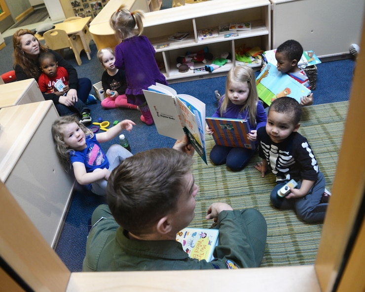 U.S. Air Force Col. John Howard, 100th Air Refueling Wing vice commander, center, reads a Dr. Seuss book to a class of children, March 3, 2017, at the Child Development Center on RAF Mildenhall, England. The CDC celebrated the author's birthday by hosting Team Mildenhall commanders, serving cake and promoting reading to their students. (U.S. Air Force photo by Senior Airman Justine Rho)