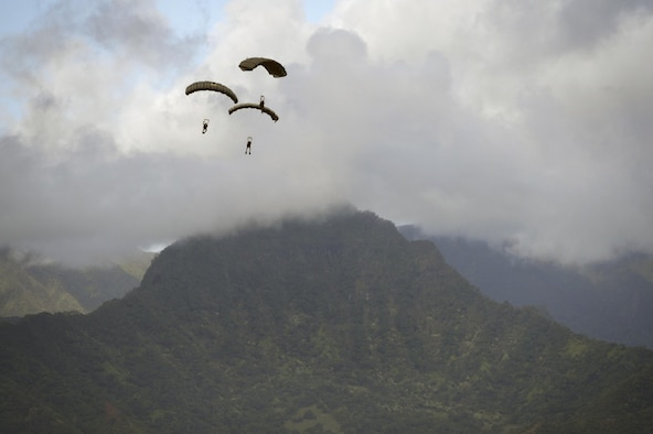 Pararescuemen and combat rescue officers from the 103rd Rescue Squadron parachute to the ground after jumping from a C-17 Globemaster III during joint training with Human Space Flight Support Detachment 3 at Marine Corps Base Hawaii, March 5 2017. (U.S. Air National Guard photo/Staff Sgt. Christopher S. Muncy)
