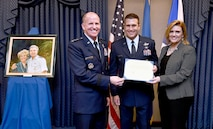 Gen. Stephen Wilson, the Air Force Vice Chief of Staff, presents the 2016 O'Malley Award to Col. John Wagner and his wife, Jennifer, during a Pentagon ceremony, March 7, 2017. The Wagners earned the award for their work at Buckley Air Force Base. Colo. (U.S. Air Force photo/Scott M. Ash)