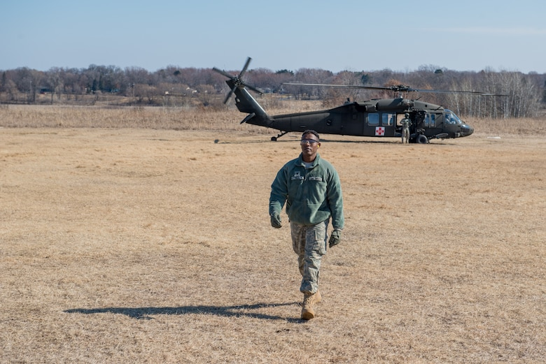 Army Specialist Mohamedkadar Idle of the 7212th Medical Support Unit walks away from a UH-60 Blackhawk helicopter during a joint service medical evacuation training on March 4th, 2017 at Arden Hills Army Training Site. (U.S. Air Force photo by Senior Airman Samuel Wacha)