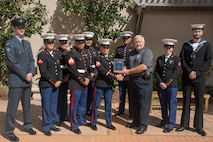 Marines from the Tri-Command Single Marines & Sailors Program receive the Senator David Thomas Award from Edgar Jansons, Port Royal Police Department, on Feb. 23, 2017, in Myrtle Beach, S.C. The award recognizes individuals or groups throughout South Carolina for their dedication to keeping their communities clean. Parris Island's 40 or so graduations each year bring tens of thousands of visitors to the local area, but one downside to that influx of people is the associated increase in litter, a problem the program members help to offset.