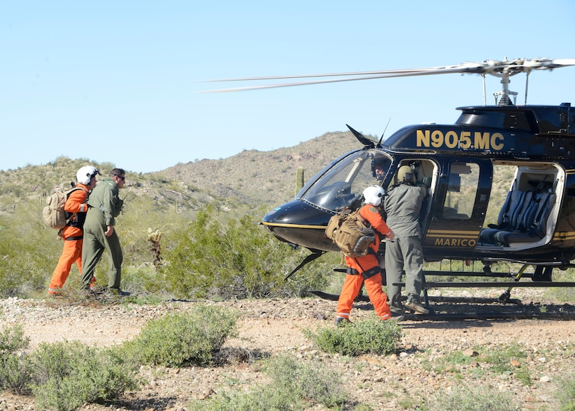 Mariacopa County Search and Rescue team guides Maj. Nicholas Suppa, 56th Operations Support Squadron  assistant director of operations, to the helicopter during a Major Accident Response Exercise at a remote area in Arizona, 1 Mar. 2017. The exercise highlighted the real way Air Force and civilian assets can be used together to more effectively respond to crises, and potentially save lives. (U.S. Air Force photo by Senior Airman Devante Williams)