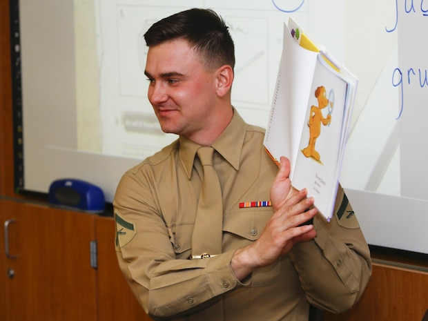Lance Cpl. Fredrick Peirce, rifleman, 3rd Battalion, 4th Marines, 7th Marine Regiment, shows pictures from a Dr. Seuss book to a 1st grade class at Palm Vista Elementary School in Twentynine Palms, Calif., as part of Read Across America Day, March 3, 2017. The battalion recently adopted the school and the unit  volunteers to participate in many of the schools' events. (U.S. Marine Corps photo by Cpl. Thomas Mudd)