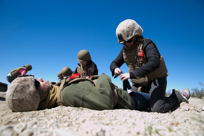Melissa Culp, wife of 1st Lt. William Culp, executive officer, company D, 1st Tank Battalion, applies a tourniquet during the battalion's Jane Wayne Day at Range 500 aboard Marine Corps Air Ground Combat Center, Twentynine Palms, Calif., March 2, 2017. The event is held to bolster unit cohesion while allowing the spouses to see what their Marines and sailors do on a daily basis. (U.S. Marine Corps photo by Cpl. Julio McGraw)