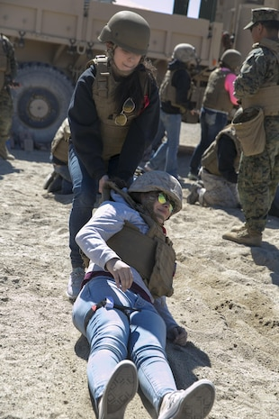 Jelanie Cisneros, wife of Sgt. Oscar Cisneros, tank commander, 1st Tank Battalion, drags Kimberle Aponte, wife of Lance Cpl. Andrew Aponte, tank gunner, 1st Tanks, during the battalion's Jane Wayne Day at Range 500 aboard Marine Corps Air Ground Combat Center, Twentynine Palms, Calif., March 2, 2017. The event is held to bolster unit cohesion while allowing the spouses to see what their Marines and sailors do on a daily basis. (U.S. Marine Corps photo by Cpl. Julio McGraw)