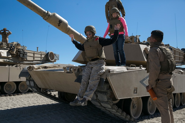 Amanda Boos, wife of Capt. Jonathon Boos, 1st Tank Battalion, sits on an M1A1 Abrams Main Battle Tank during the battalion's Jane Wayne Day at Range 500 aboard Marine Corps Air Ground Combat Center, Twentynine Palms, Calif., March 2, 2017. The event is held to bolster unit cohesion while allowing the spouses to see what their Marines and sailors do on a daily basis. (U.S. Marine Corps photo by Cpl. Julio McGraw)