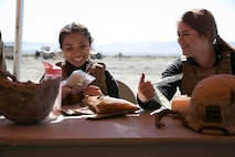 Mari Saucedo, wife of HM3 Eduardo Saucedo, corpsman, 1st Tank Battalion, eats a Meal Ready-to-Eat lunch with Codi Trifiro, wife of Lance Cpl. Shane Trifiro, 1st Tank Battalion, during the battalion's Jane Wayne Day at Range 500 aboard Marine Corps Air Ground Combat Center, Twentynine Palms, Calif., March 2, 2017. The event is held to bolster unit cohesion while allowing the spouses to see what their Marines and sailors do on a daily basis. (U.S. Marine Corps photo by Cpl. Julio McGraw)
