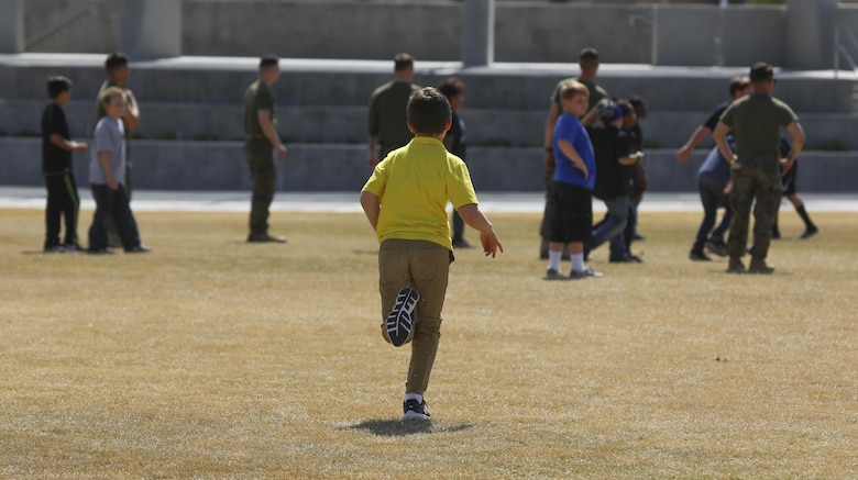 Fourth and fifth-grade students from Palm Vista Elementary school play kickball with Marines from 3rd Battalion, 4th Marines, 7th Marine Regiment at Victory Park following the annual Battle Color Ceremony at Lance Cpl. Torrey L. Gray Field aboard Marine Corps Air Ground Combat Center, Twentynine Palms, Calif., March 8, 2017. 3/4 adopted the elementary school in order to mentor the children.  (U.S. Marine Corps photo by Lance Cpl. Natalia Cuevas)