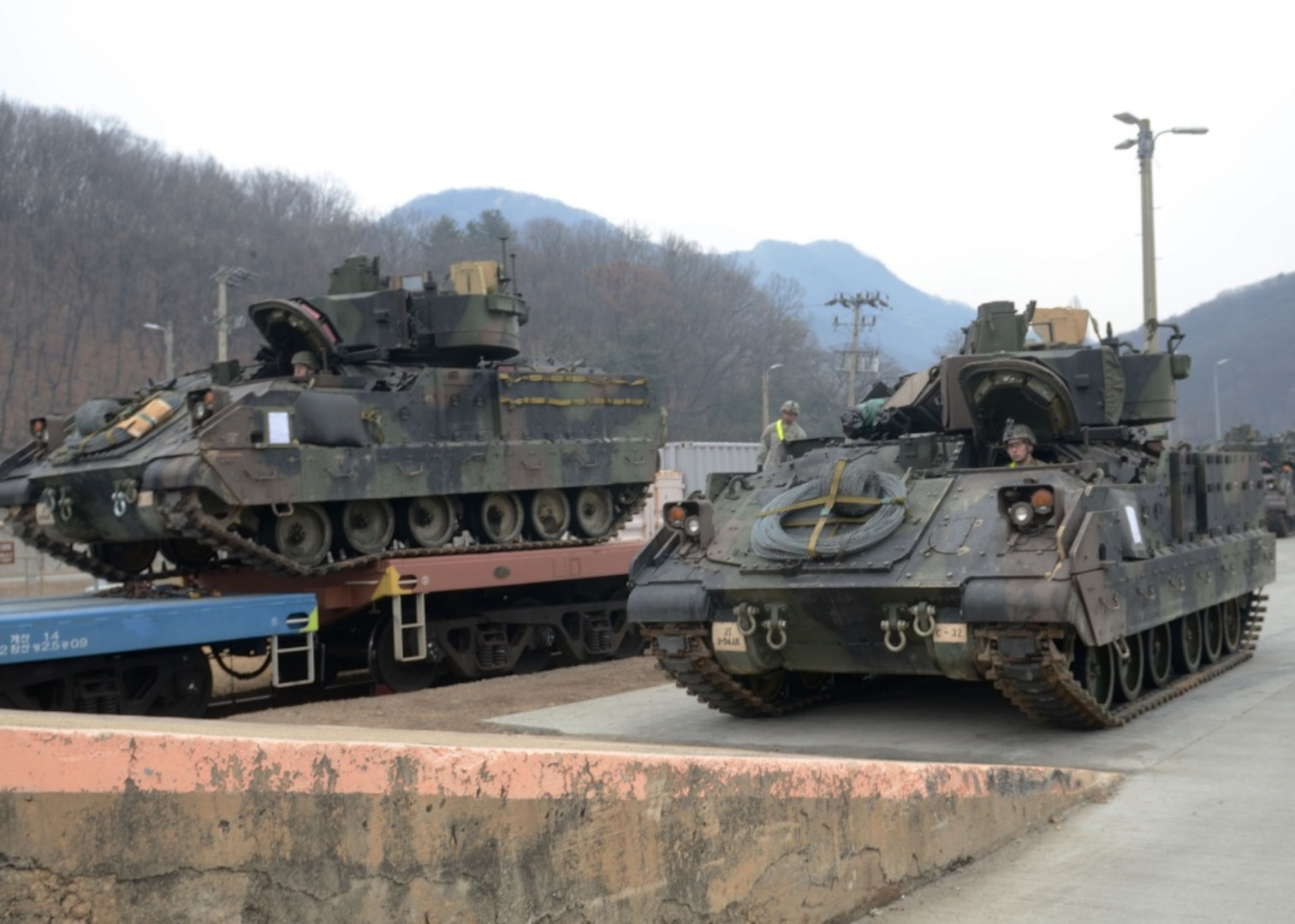 Soldiers from 2nd Battalion, 34th Armor Regiment, 1st Armored Brigade Combat Team, 1st Infantry Division, load their M2 Bradley Infantry Fighting Vehicles onto rail cars during relocation operations at the Camp Casey rail yard Feb. 22. The battalion is the first of the 1st ABCT's units to conduct the move to Camp Humphreys in Pyeongtaek, South Korea.