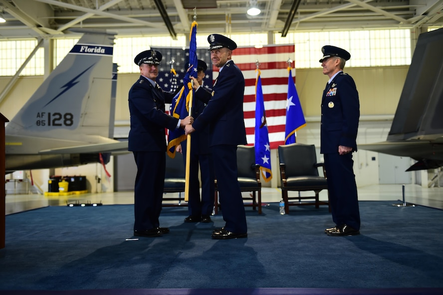 """U.S. Air Force Chief of Staff Gen. David L. Goldfein passes the Air Combat Command guidon to Gen. James M. Holmes during ACC's Change of Command ceremony at Joint Base Langley-Eustis, Va., March 10, 2017. Holmes assumed command from Gen. Herbert """"Hawk"""" Carlisle, who retired after 39 years of service to the Air Force. (U.S. Air Force photo/Senior Airman Kimberly Nagle)"""