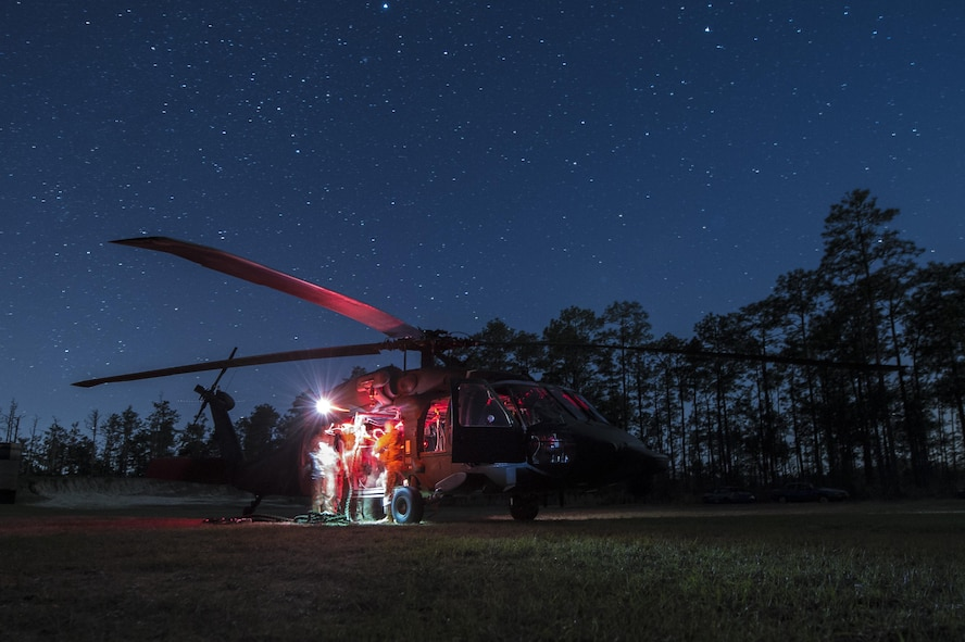 Members of the 7th Special Forces Group attatch a hoist to U.S. Army UH-60L Black Hawk at Eglin Air Force Base, Fla., March 3, 2017 during Emerald Warrior 17. Emerald Warrior is a U.S. Special Operations Command exercise during which joint special operations forces train to respond to various threats across the spectrum of conflict. (U.S. Air Force photo/Airman 1st Class Keifer Bowes)