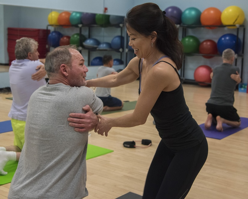 Le Nguyen, right, West Fitness Center yoga instructor, assists a student with a pose during her yoga class at Joint Base Andrews, Md., March 9, 2017. Nguyen has been a JBA volunteer yoga instructor since October 2015. While she teaches, she focuses on the overall class and on students individually. (U.S. Air Force photo by Airman 1st Class Valentina Lopez)
