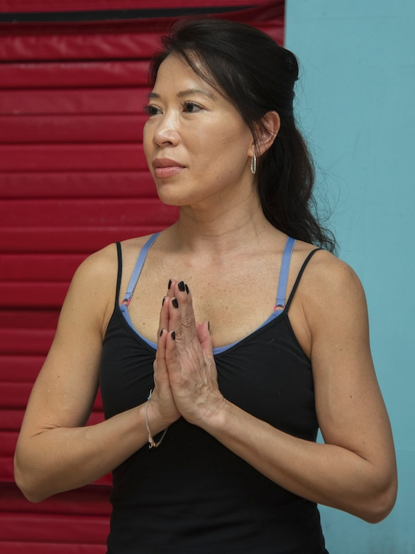 Le Nguyen, West Fitness Center yoga instructor, holds her hands together during her yoga class at Joint Base Andrews, Md., March 9, 2017. Nguyen has been volunteering at JBA as a yoga instructor since October 2015 and has been practicing yoga for eight years. (U.S. Air Force photo by Airman 1st Class Valentina Lopez)