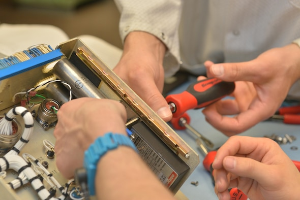 Technicians from the 791st Maintenance Squadron electronics laboratory remove screws from a controller monitor at Minot Air Force Base, N.D., March 2, 2017. Electronic laboratory technicians inspect, troubleshoot, and repair electronic components and test equipment for launch facilities, and launch control centers. (U.S. Air Force photo/Airman 1st Class Jessica Weissman)