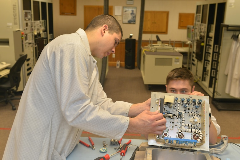 (From left) Staff Sgt. Dylan Wood, 791st Maintenance Squadron electronics laboratory trainer, and Senior Airman Maxwell Clement, 791st MXS ELAB technician, remove faulty components from a controller monitor at Minot Air Force Base, N.D., March 2, 2017. Electronic laboratory technicians are responsible for maintenance and quality assurance of the Minuteman III Intercontinental Ballistic Missile support equipment. (U.S. Air Force photo/Airman 1st Class Jessica Weissman)