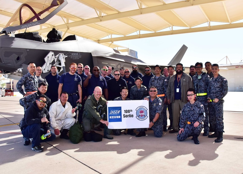 Members from the Japan Air Self-Defense Force, Lockheed Martin, and 944th Operations Group Detachment 2, pose for a photo Mar. 7 after the 100th sortie milestone at Luke Air Force Base, Ariz. (U.S. Air Force photo by Tech. Sgt. Louis Vega Jr.)