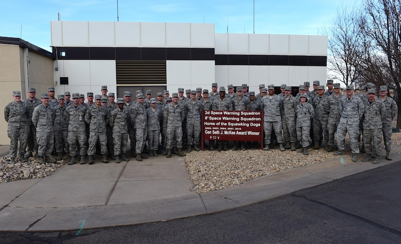"Members of the 2nd Space Warning Squadron pose for a photo March 10, 2017, around the Gen. Seth J. McKee award sign on Buckley Air Force Base, Colo. The McKee award was presented to the 2nd SWS for being recognized as the best missile warning squadron of 2016 in the Air Force Space Command. The ""2016"" is yet to be installed on the sign. (U.S. Air Force photo by Airman Jacob Deatherage/Released)"