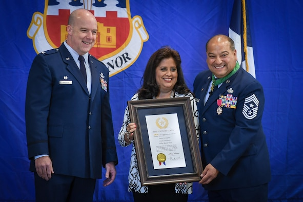 """Command Chief Master Sgt. George B. Longoria (right) and his wife, Patty, hold a certificate signed by Texas Gov. Greg Abbott honoring Patty as a """"Yellow Rose of Texas"""" for her support of Longoria during his military career at Joint Base San Antonio-Lackland, Texas, Feb. 25, 2017. The Longorias are joined by Col. Timothy Madden, commander of the 149th Fighter Wing, Texas Air National Guard. Longoria retires after 35 years of military service. (U.S. Air National Guard photo by Tech. Sgt. Eric L. Wilson)"""