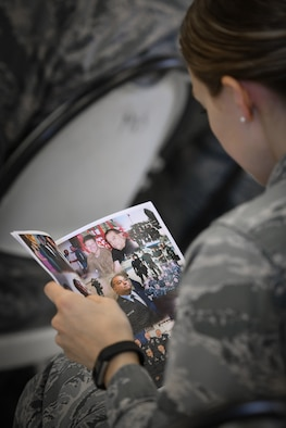 1st Lt. Melissa Spencer, wing executive officer, looks at images of Command Chief Master Sgt. George B. Longoria, during a retirement ceremony honoring Longoria at Joint Base San Antonio-Lackland, Texas, Feb. 25, 2017. Longoria retires after 35 years of service with the 149th Fighter Wing, Texas Air National Guard. (U.S. Air National Guard photo by Tech. Sgt. Eric L. Wilson)