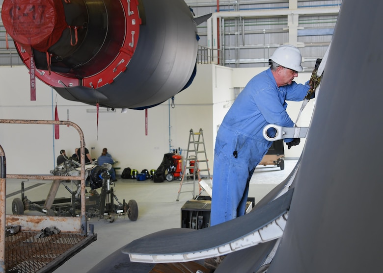Bruce Natale, a contractor mechanic with Boeing, works on a U.S. Air Force C-17 Globemaster III at Al Udeid Air Base, Qatar, Feb. 25, 2017. The C-17 aircraft was lifted up inside a Qatari hangar in order to allow maintenance on it without interruption from the weather. (U.S. Air Force photo by Senior Airman Miles Wilson)