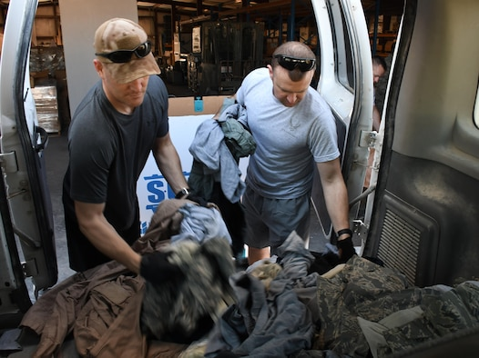 U.S. Airmen unload a van full of uniform items at Al Udeid Air Base, Qatar, March 10, 2017. The uniform items were gathered by volunteers from the uniform disposal bins located around the base, and then were sorted and shredded. (U.S. Air Force photo by Senior Airman Miles Wilson)