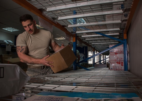 Airman Brent Downs, a 386th Expeditionary Logistics Readiness Squadron supply journeyman, places a box in its designated location at the post office here March 11, 2017. Post office contractors and volunteers sort and stow mail not only for the 386th but other branches and coalition partners around base as well.  (U.S. Air Force photo illustration/Senior Airman Andrew Park)