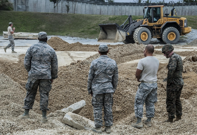 U.S. Air Force Staff Sgt. Chue Her, Airman Brandon Mclendon and Senior Airman Justin Hewitt, 18th Civil Engineer Group pavement maintenance and heavy equipment operator demonstrate procedures for airfield damage repair at the munitions storage area of Kadena Air Base, Japan, March 3, 2017. The exercise took place March 2-3, allowing members of the Air Force, Navy and Marine Corps to demonstrate their capabilities. (U.S. Air Force photo by Senior Airman Nick Emerick/Released)